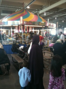 A Muslim wearing an abaya watches a carousel spin.